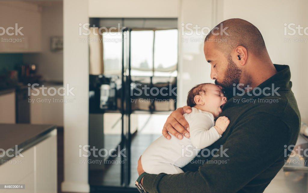 Cute niño pequeño en brazos de su padre - foto de stock