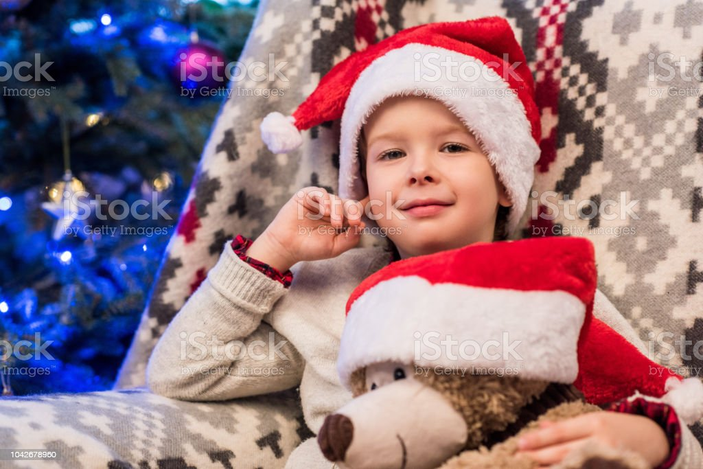 70696c2e78142 Cute little boy in santa hat holding teddy bear and smiling at camera at  christmas time - Stock image .