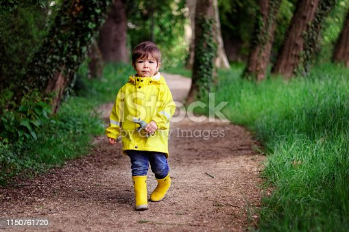 Cute little boy in yellow raincoat and rubber boots holding rhino toy with scared face walking alone lost in dark green forest. Childhood concept