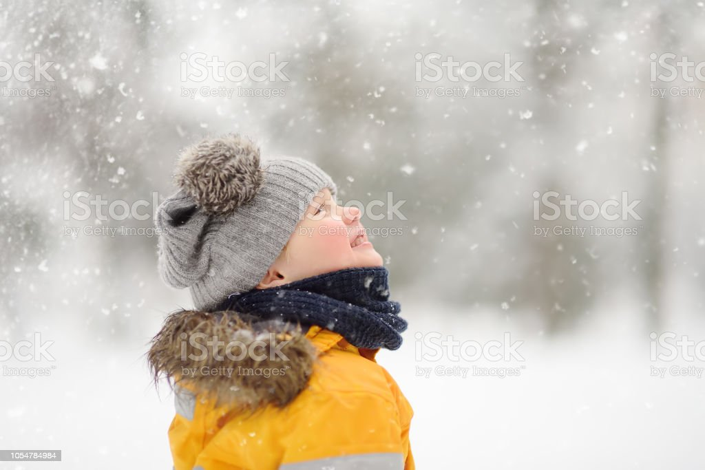 Cute little boy in yellow winter clothes walks during a snowfall stock photo