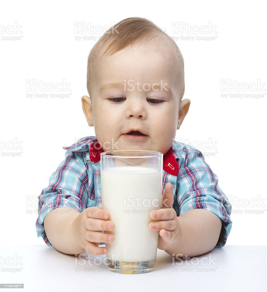 Cute little boy is holding big glass of milk stock photo