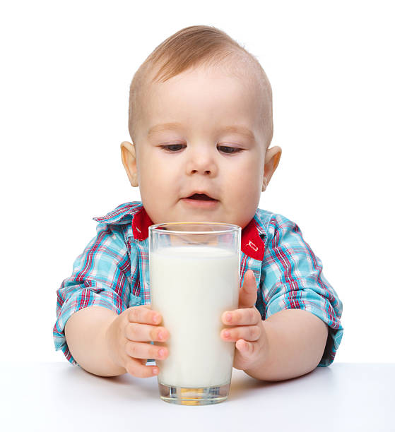 Cute little boy is holding big glass of milk stock photo