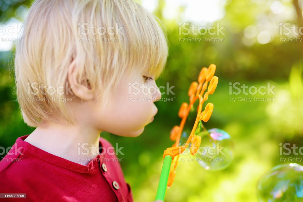 Cute little boy is playing with big bubbles outdoor. Child is blowing...