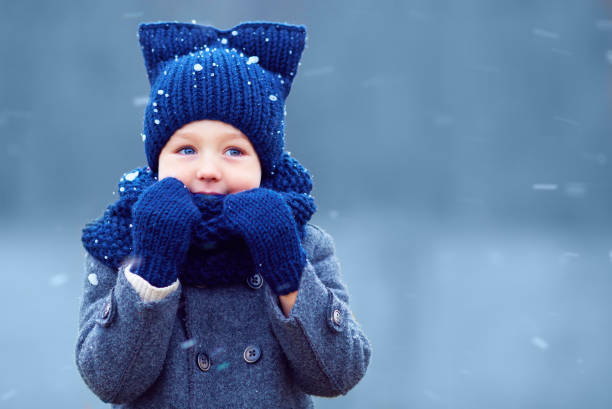 cute little boy, kid in winter clothes walking under the snow cute little boy, kid in winter clothes walking under the snow warm clothing stock pictures, royalty-free photos & images
