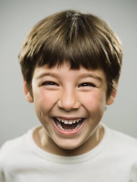 niedliche kleine junge lachend im studio - buben stock-fotos und bilder