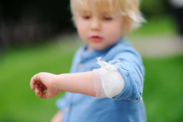 Mignon petit garçon à la recherche sur son coude avec bandage appliqué - Photo