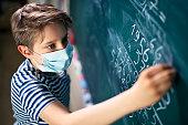 Little boy wearing face mask doing math calculations.\nNikon D850