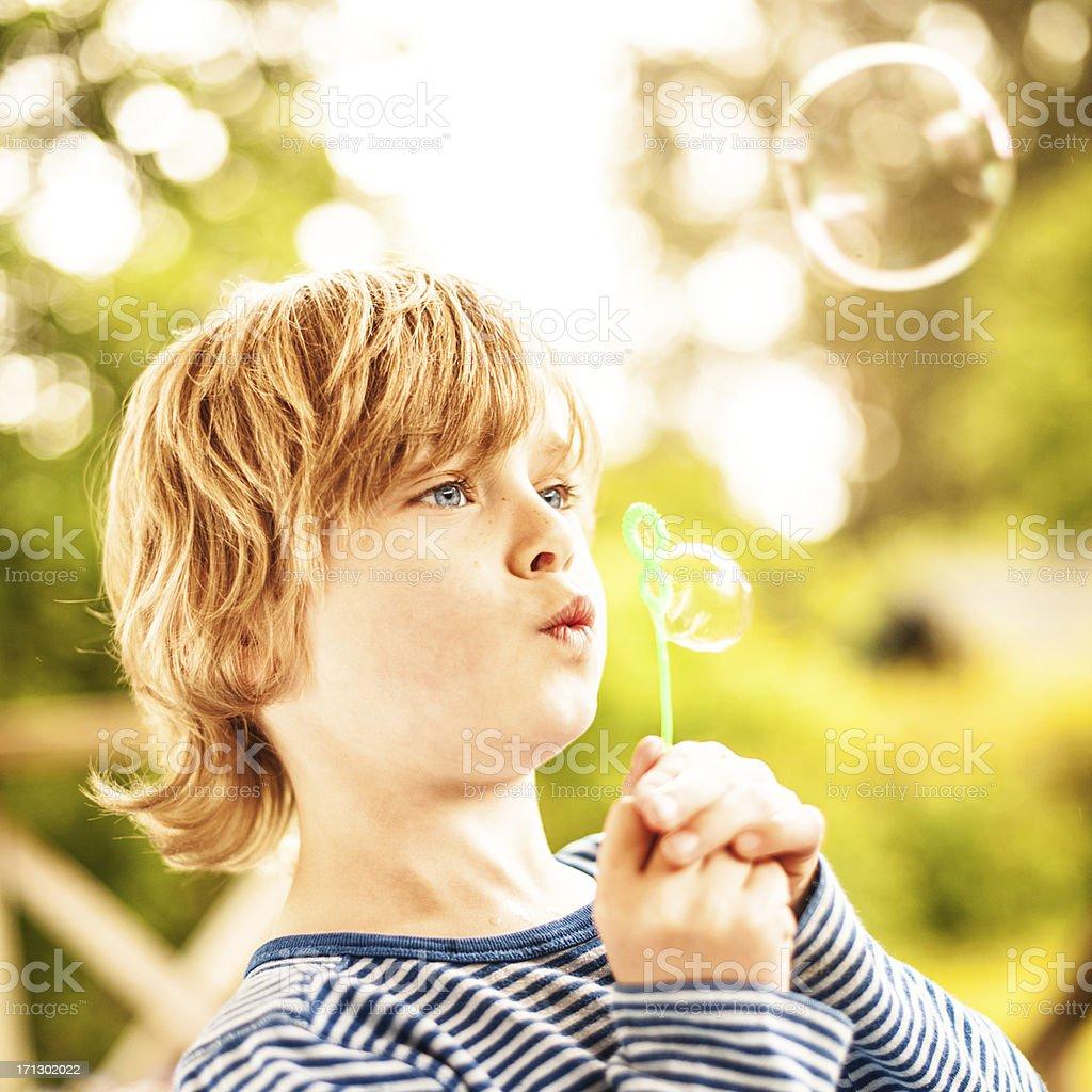 Cute little boy outdoors blowing bubbles stock photo