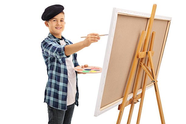 Cute little boy painting on a canvas Cute little boy with a black beret painting on a canvas and looking at the camera isolated on white background beret stock pictures, royalty-free photos & images