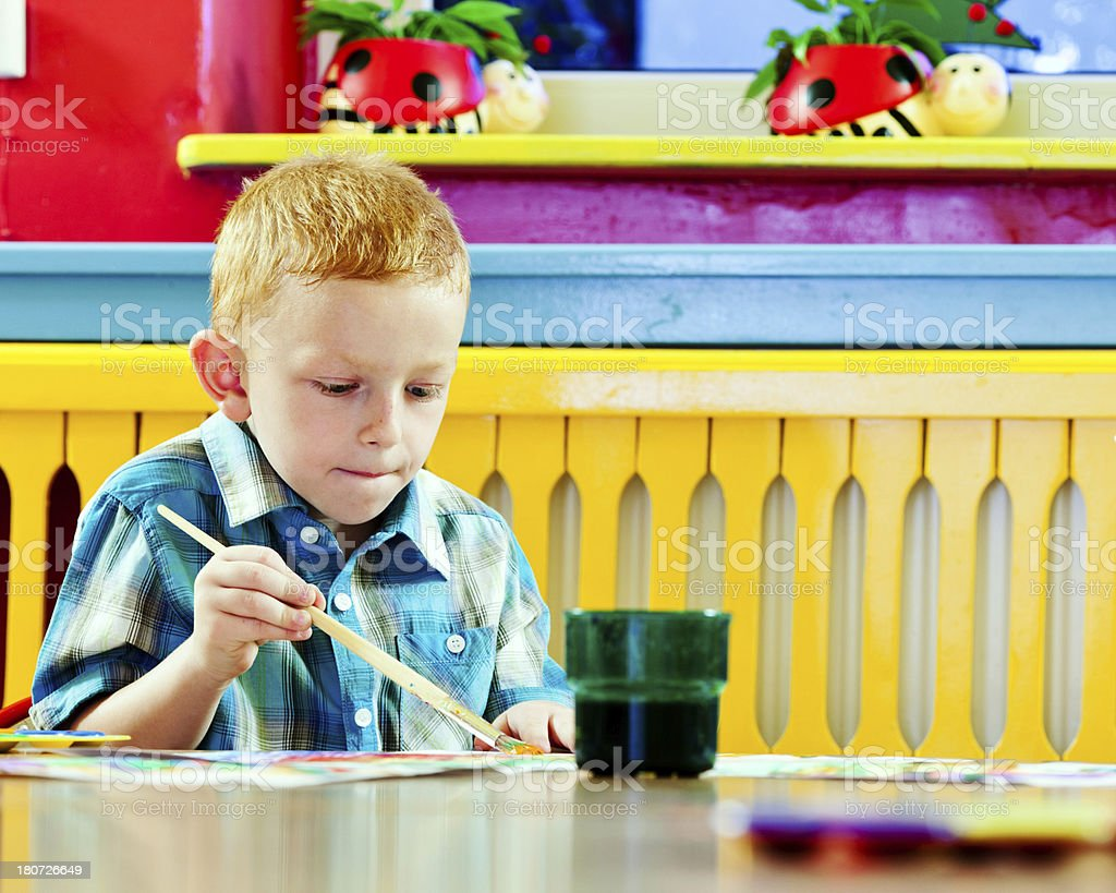 Cute Little Boy Painting A cute preschool boy sitting at the table in classroom and painting.  4-5 Years Stock Photo