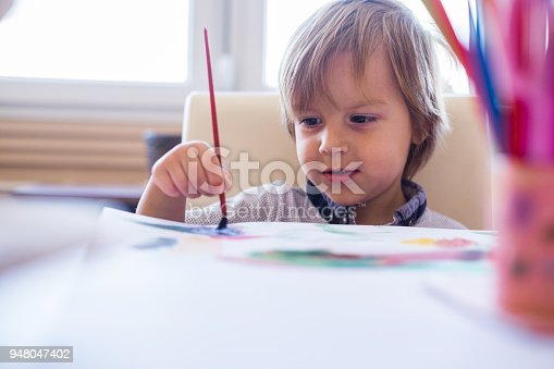 istock Cute little boy painting with water colors 948047402
