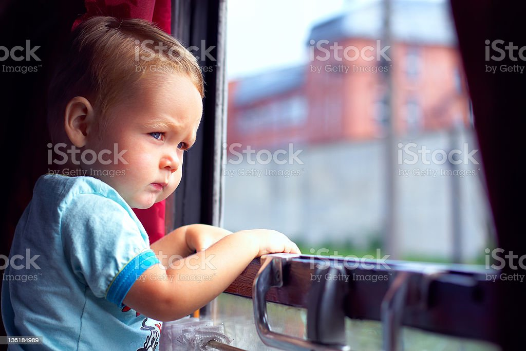 cute little boy picking out from train window outside royalty-free stock photo