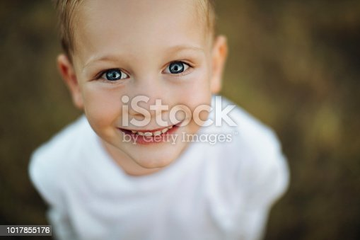 Close up portrait of a cute little boy smiling at the camera outdoors
