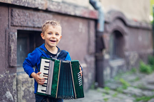 Cute little boy playing accordion stock photo