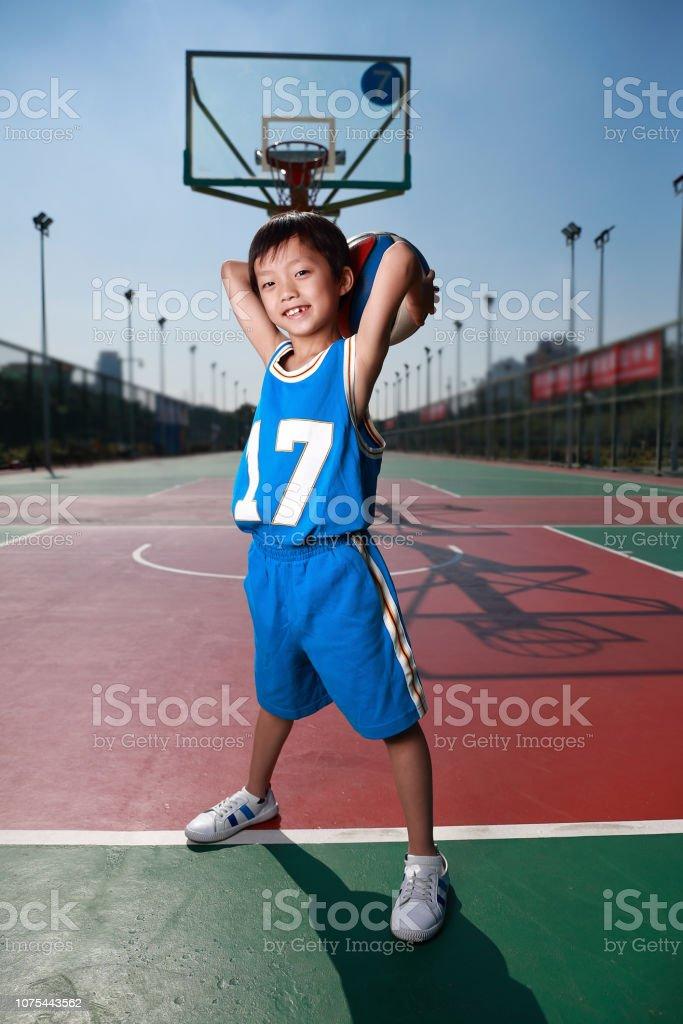 Cute little boy playing basketball stock photo