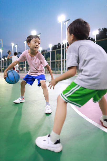 Cute little boy playing basketball stock photo