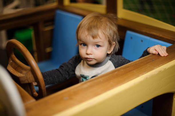 niedlichen kleinen jungen spielen in das spielzeugauto aus holz - rudermaschine stock-fotos und bilder