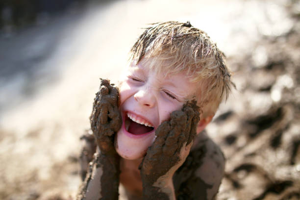 Cute Little Boy Playing Outside in the Mud with a Dirty Face stock photo