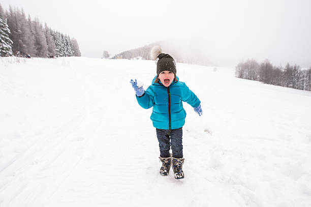 cute little boy playing outside in winter nature - kinder winterstiefel stock-fotos und bilder