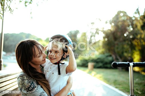 Cute little boy playing outside with his mom. Safety in the first place!
