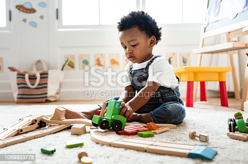 istock Cute little boy playing with a railroad train toy 1069933778