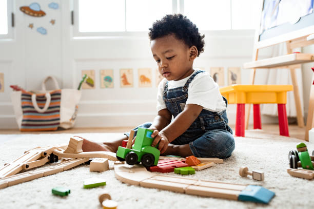 Cute little boy playing with a railroad train toy Cute little boy playing with a railroad train toy baby human age stock pictures, royalty-free photos & images