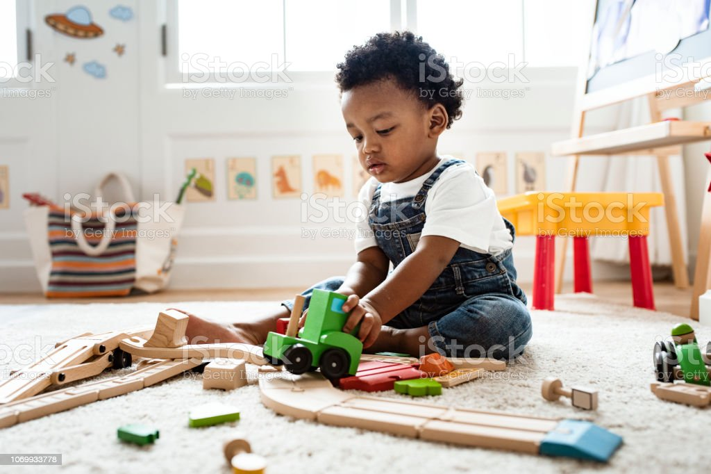 Cute little boy playing with a railroad train toy stock photo
