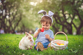 Happy little boy playing with bunny in park on Easter egg hunt