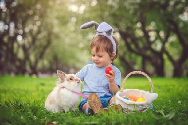 Niedlicher kleiner Junge, der mit Hasen und Ostereiern spielt – Foto