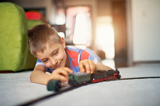 Happy little boy lying on a carpet, playing with miniature train. Very shallow depth of field. Sunny day indoors.