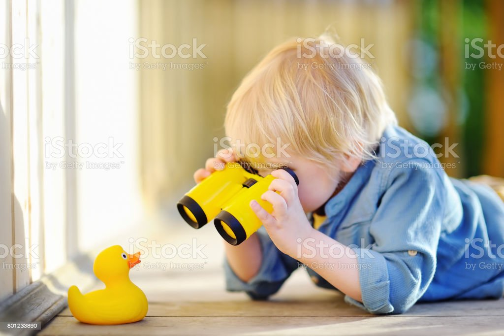 Cute little boy playing with rubber duck and plastic binoculars outdoors royalty-free stock photo