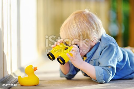 istock Cute little boy playing with rubber duck and plastic binoculars outdoors 801233890