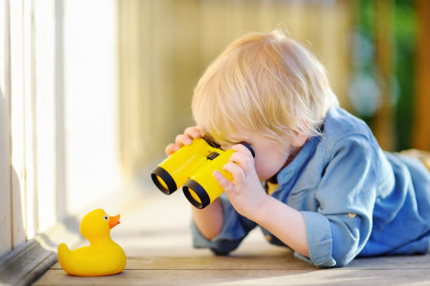 Cute little boy playing with rubber duck and plastic binoculars outdoors stock photo