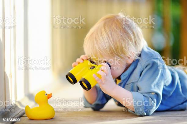Photo of Cute little boy playing with rubber duck and plastic binoculars outdoors