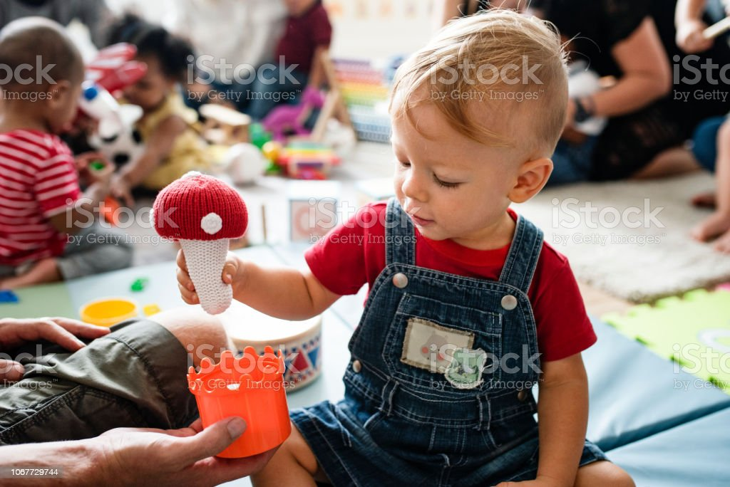 Cute little boy playing with toys at the learning center stock photo