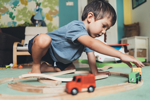 Cute little boy playing with wooden train on the floor at home