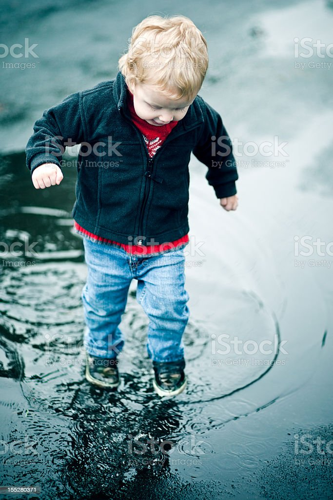 Cute Little Boy Plays in Puddle royalty-free stock photo