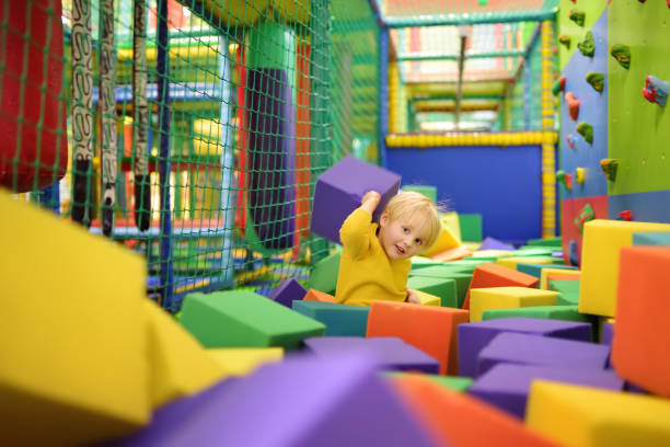 cute little boy plays with soft cubes in the dry pool in play center. kid playing on indoor playground in foam rubber pit in trampoline. - suavidade imagens e fotografias de stock