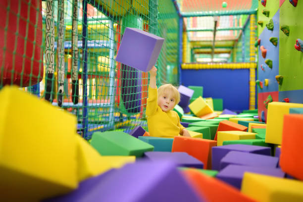 Lindo niñito juega con cubos blandos en la piscina seca en el centro de juego. Kid jugando en el patio interior en el pozo de goma de espuma en trampolín. - foto de stock