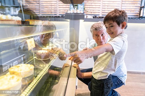 Cute little boy pointing at the retail display the dessert he wants while grandfather kneels next to him at the bakery