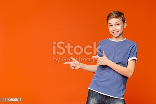 istock Cute little boy pointing away on orange background 1140606817