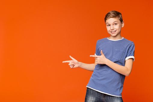 istock Cute little boy pointing away on orange background 1140606817