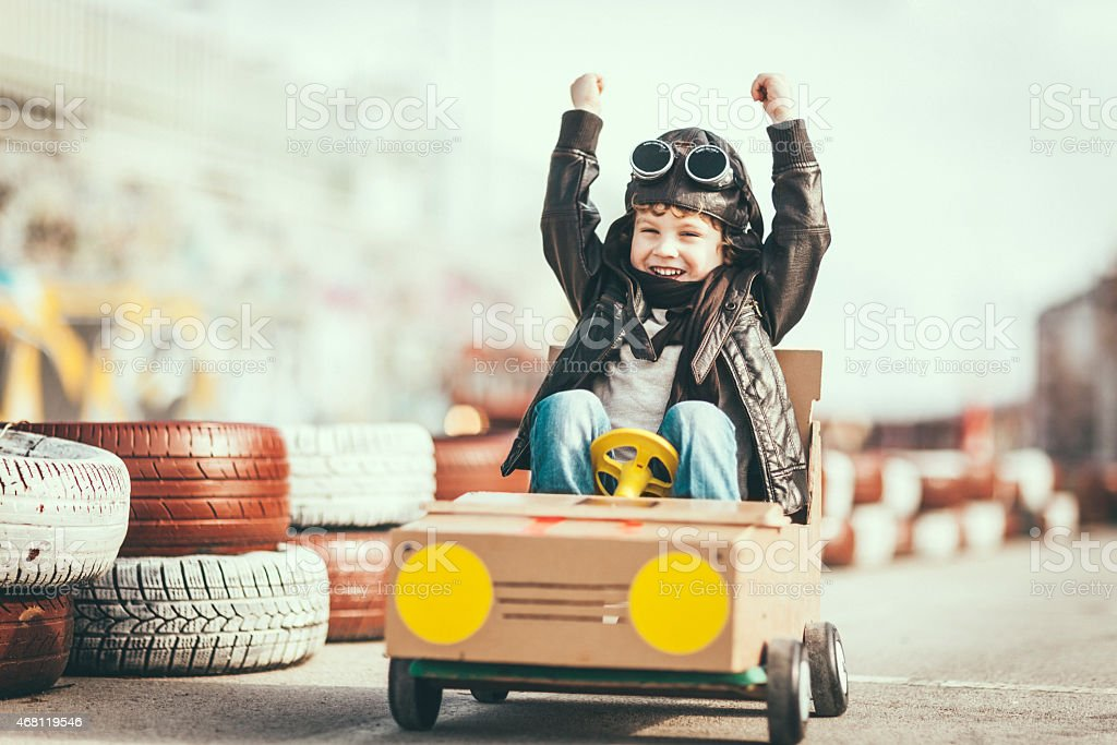 Cute little boy racing in a vintage go kart stock photo