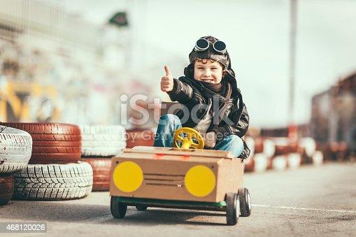 959599892 istock photo Cute little boy racing in a vintage go kart 468120026
