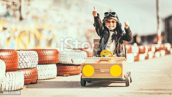 959599892 istock photo Cute little boy racing in a vintage go kart 468120188