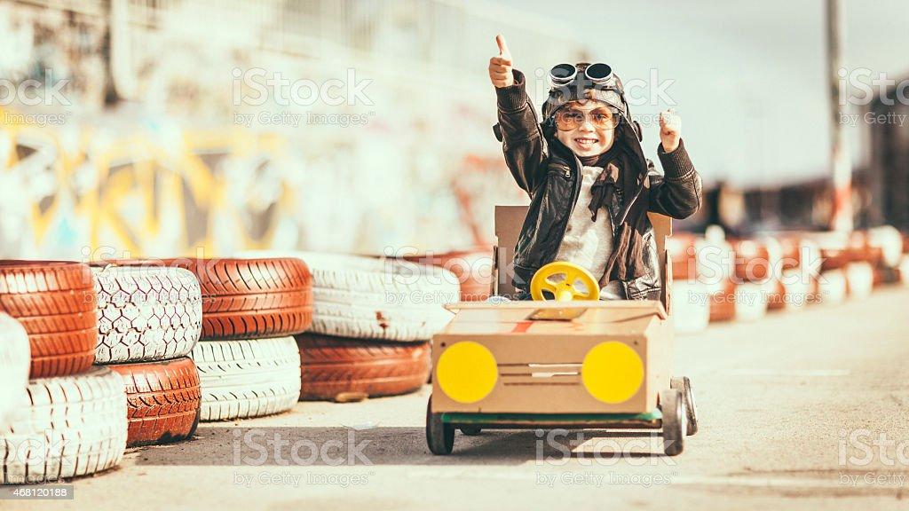 Cute little boy racing in a vintage go kart stock photo