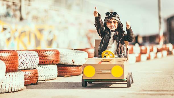 süße kleine junge racing in einem vintage-go-kart - kleine jungen kostüme stock-fotos und bilder