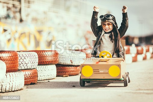 Happy little vintage racer, racing in a handmade wooden go kart, on a kart circuit. Little boy is dressed in leather jacket and wears protective helmet and glasses. He is smiling and proudly driving his go kart / celebrating his win / giving thumbs up after winning. Rubber tires partially visible on the side of the track. Retro revival concept. Outdoor shot.