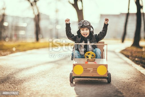 1035136022istockphoto Cute little boy racing in a vintage go kart 468420632