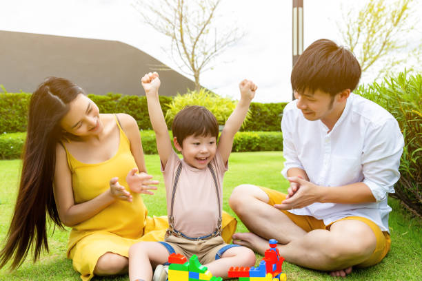 Cute little boy raise hands up and get happiness that kid can finish homework. Mother and father give son a big hand for encouraging their cute son with smiley faces. They are happy and warm family stock photo